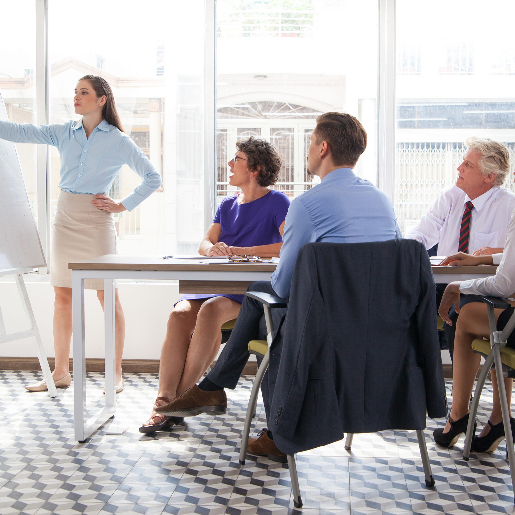Confident female business coach pointing at whiteboard and explaining graph at meeting, group of four people listening to her. They sitting in conference room. Business training or education concept